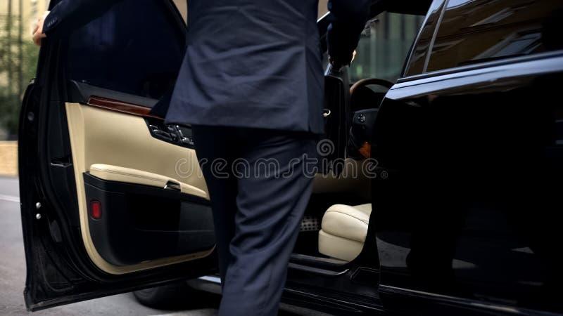 进入豪华汽车的商人,驾驶到重要会议,千福年 免版税库存照片