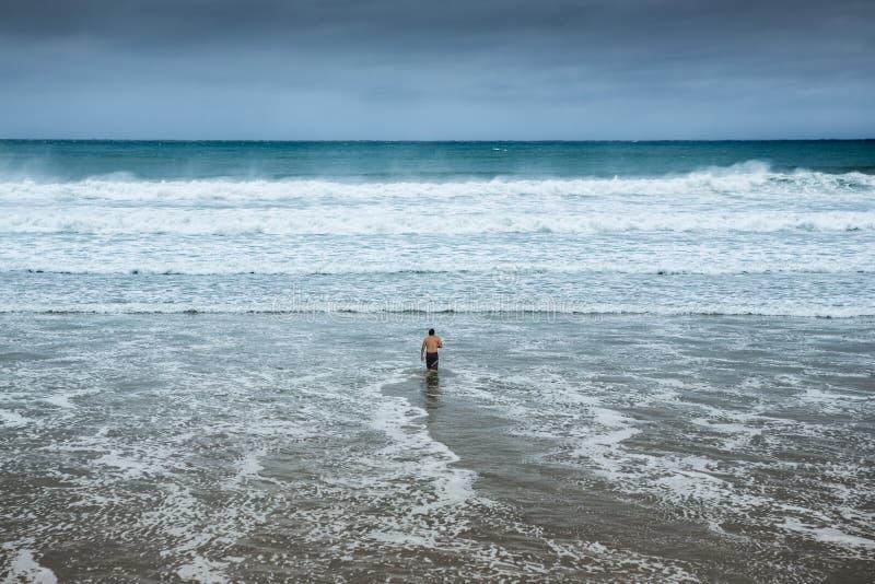 进入水的孤独的人在阴暗海滩 免版税库存照片