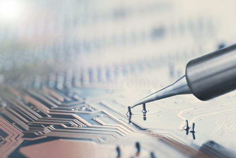 进展中的工作 焊接与电子元件的电子线路板 焊接的岗位 工程师修理电路bo 免版税库存图片