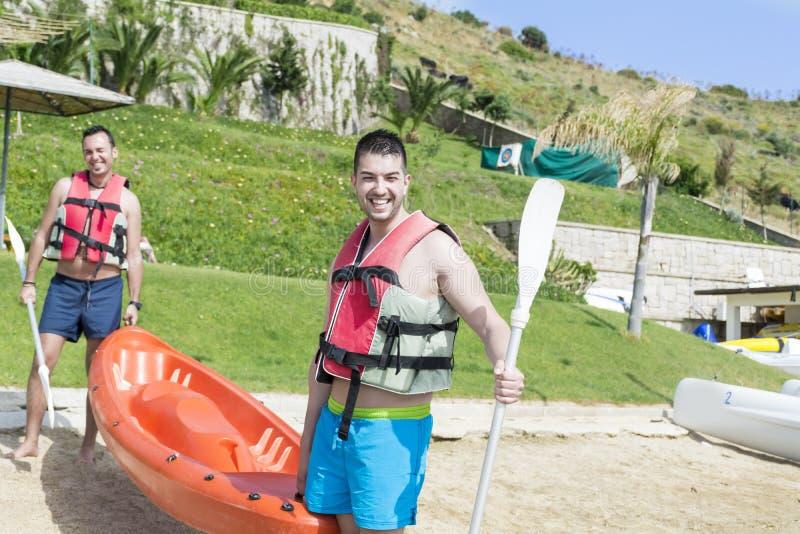 进来在有橙色独木舟的海的两个年轻朋友 库存照片