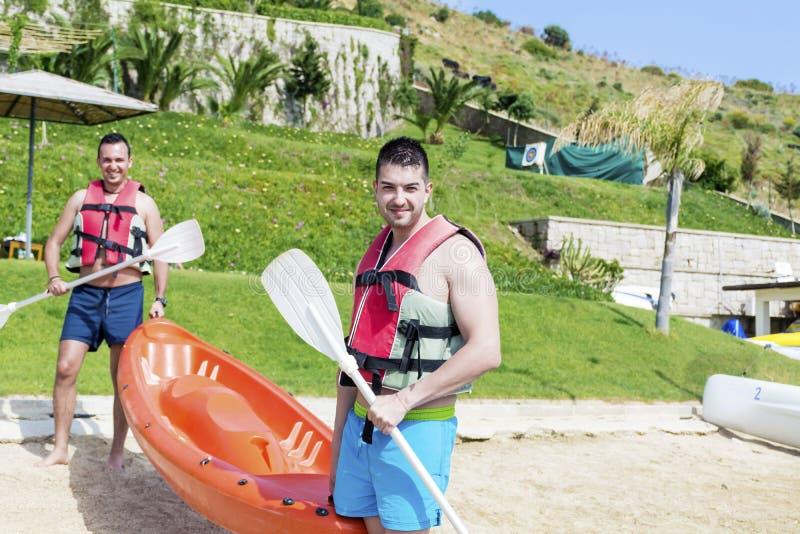 进来在有橙色独木舟的海的两个年轻朋友 免版税库存图片