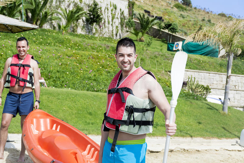 进来在有独木舟的海的两个年轻朋友 图库摄影