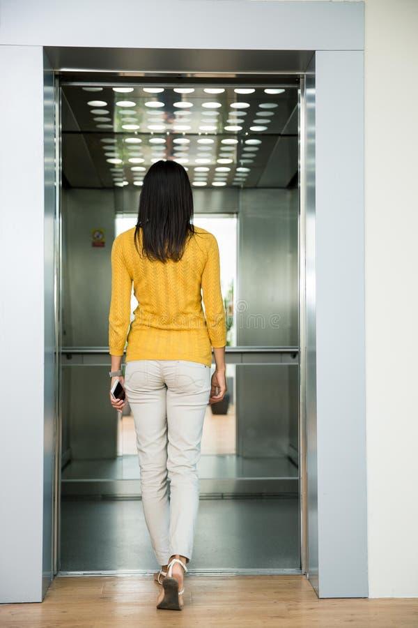 进来在电梯的妇女的后面看法画象 免版税库存照片