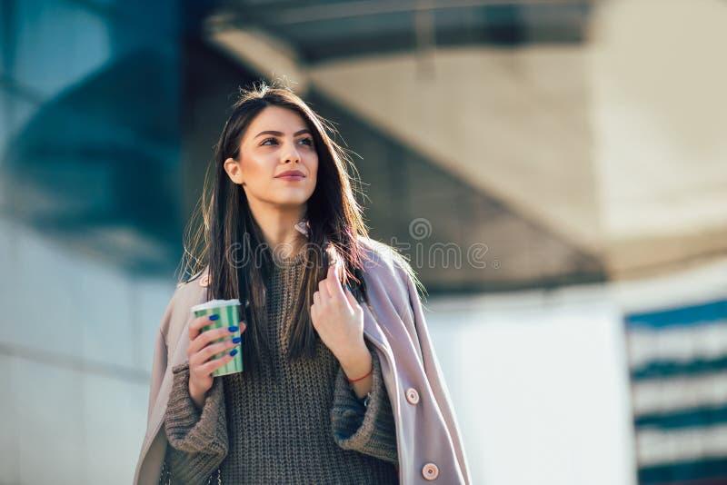 进来的妇女饮用的咖啡在城市街道 库存图片