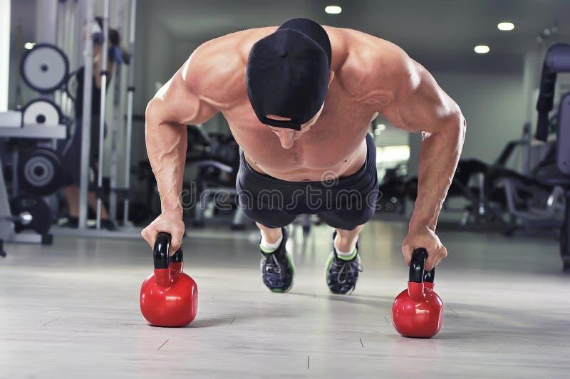 进行俯卧撑的英俊的强有力的运动人与水壶响铃 免版税库存照片