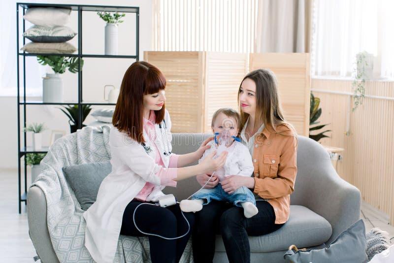 进行医学在一个小女婴的医生吸入治疗由吸入器面具  库存照片