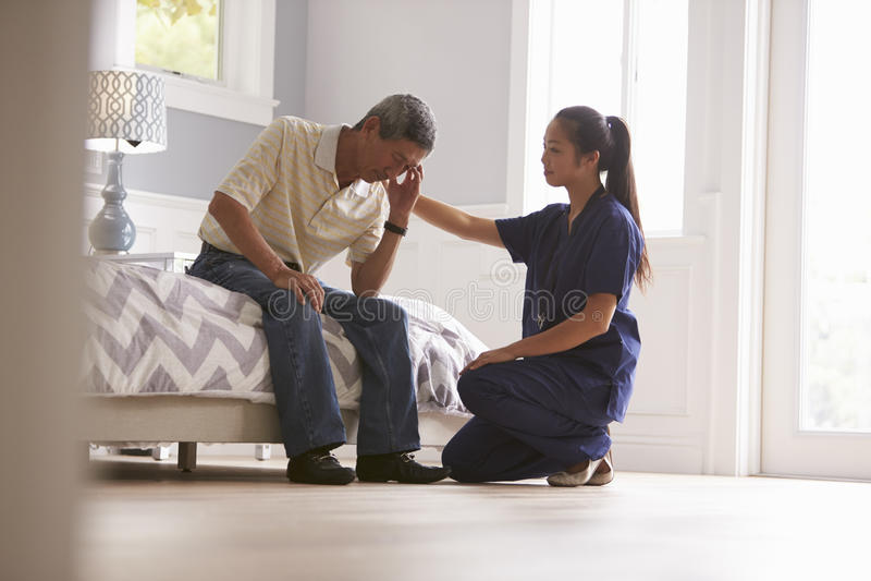 进行在家访问的护士对沮丧的老人 免版税库存图片