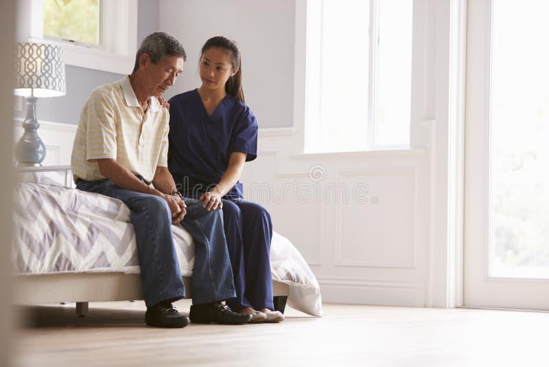 进行在家访问的护士对沮丧的老人 库存图片