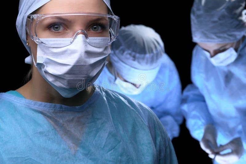 进行操作的医疗队 在女性医生的焦点 免版税库存图片
