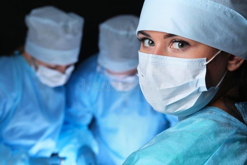 进行操作的外科医生特写镜头  在女性护士的焦点 医学、手术和紧急帮助概念 免版税库存照片