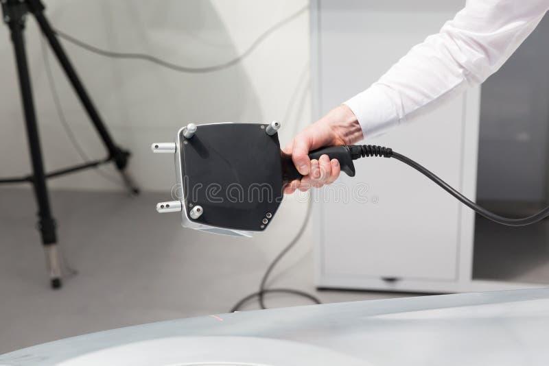 进行质量管理或检查的计量学工程师与手扶的专业3D激光扫描器 免版税图库摄影