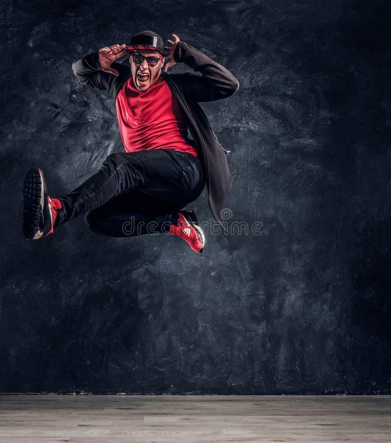 进行霹雳舞跳跃的情感时髦的打扮的人 免版税库存图片
