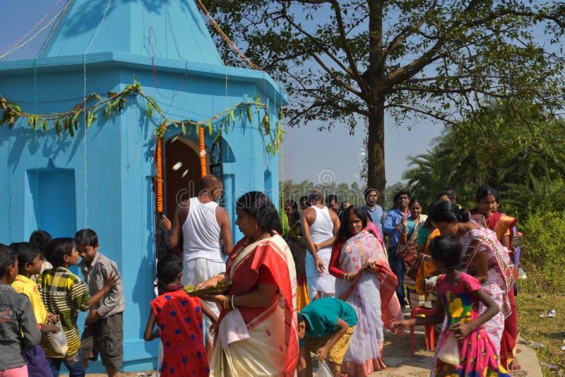 进行puja仪式通过走围绕寺庙和分布甜点的有些男人和妇女对孩子 免版税库存图片