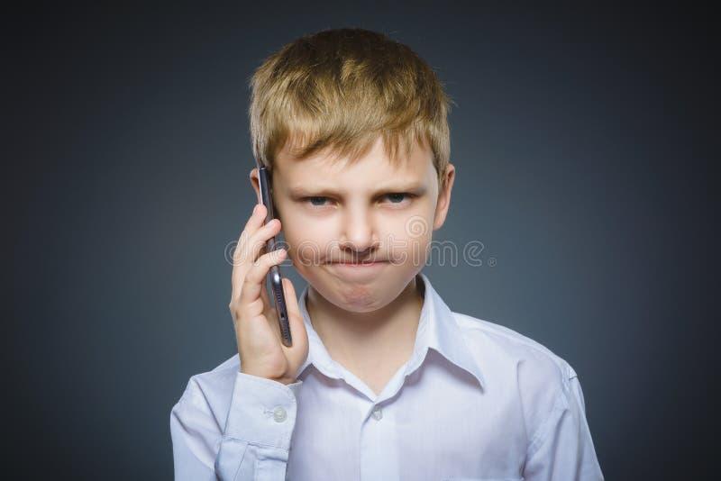 进攻男孩画象有机动性或手机的 消极人的情感 免版税库存照片