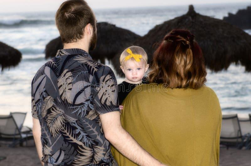 远离照相机的母亲&父亲面孔与看与婴孩的婴孩照相机观看在墨西哥设置的太阳 库存图片