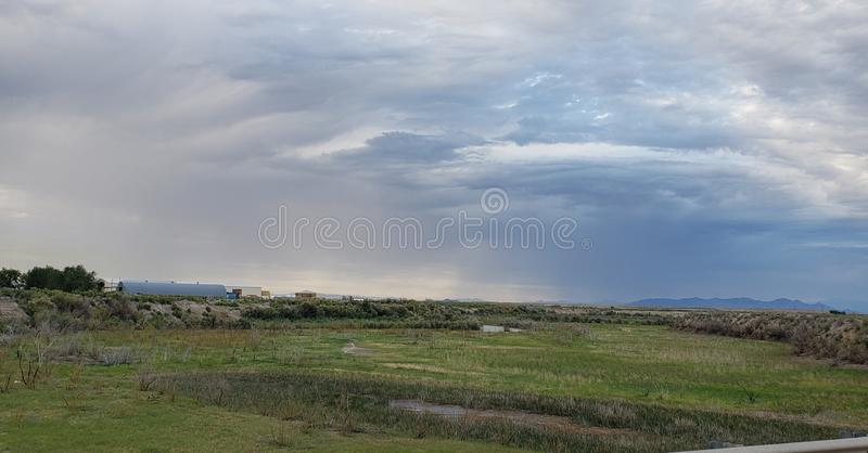 远背景风暴的乡村景观河 免版税库存图片