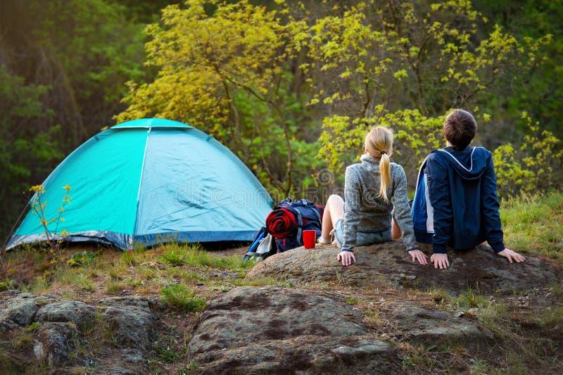 远足与背包的年轻夫妇休息在的帐篷附近 免版税库存照片