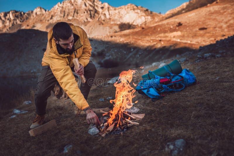 远足人在山的点燃木柴 免版税图库摄影