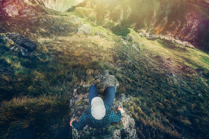 远足人坐峭壁与山鸟瞰图旅行生活方式冒险假期概念的桥梁边缘 免版税库存照片