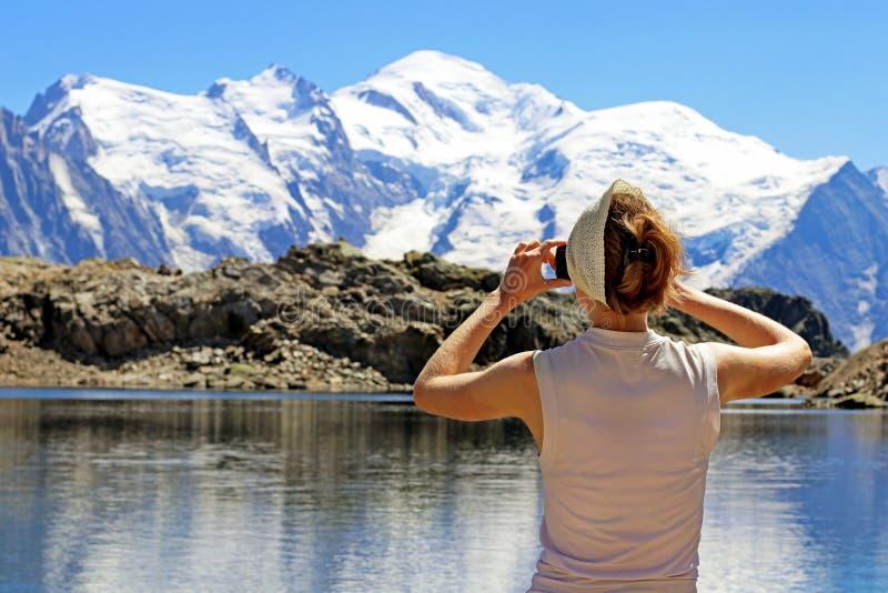 远足使用巧妙的电话的妇女拍勃朗峰山顶照片从努瓦尔的紫胶的,夏慕尼,法国 免版税图库摄影