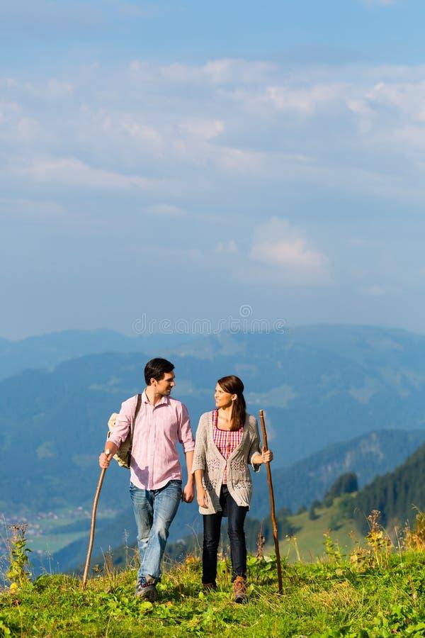 远足假期-男人和妇女阿尔卑斯山的 免版税库存照片