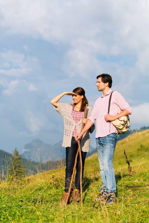 远足假期-男人和妇女阿尔卑斯山的 库存照片
