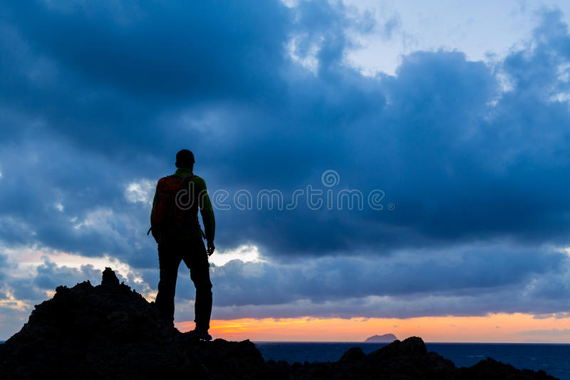 远足剪影背包徒步旅行者,激动人心的日落风景 库存图片