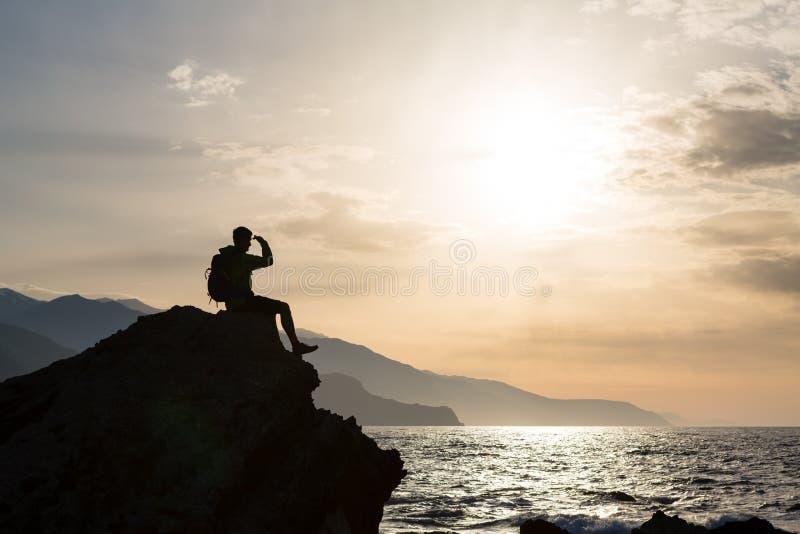 远足剪影背包徒步旅行者,看海洋的人 库存图片