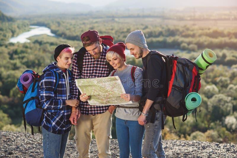 远足和看地图的人在他们的冒险期间 两个男人和两名妇女,探索山的徒步旅行者 库存照片