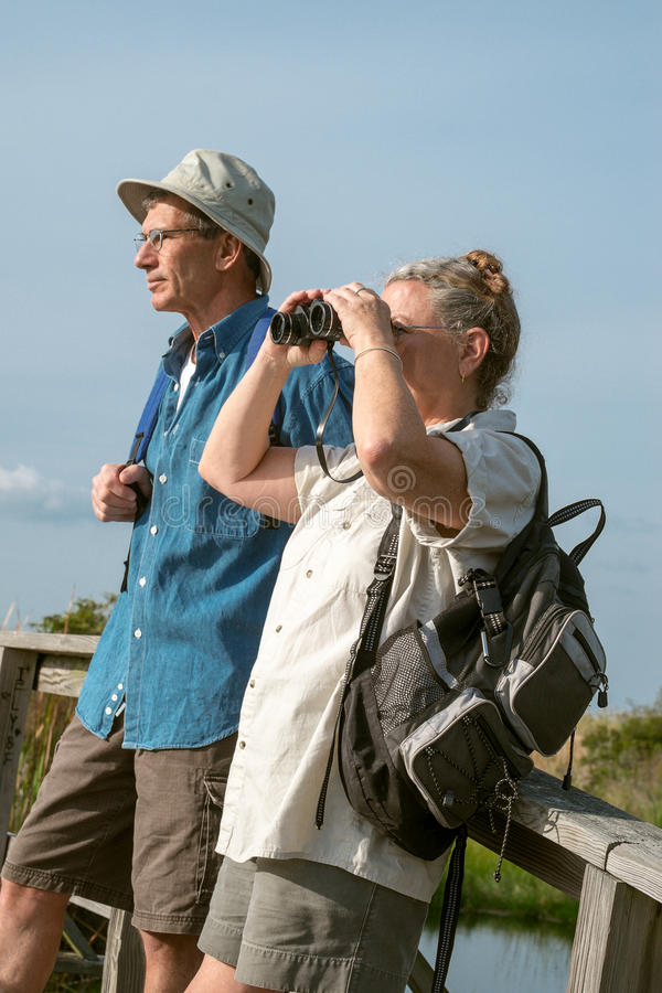 远足和鸟的监视人与Binocul的资深夫妇 库存照片