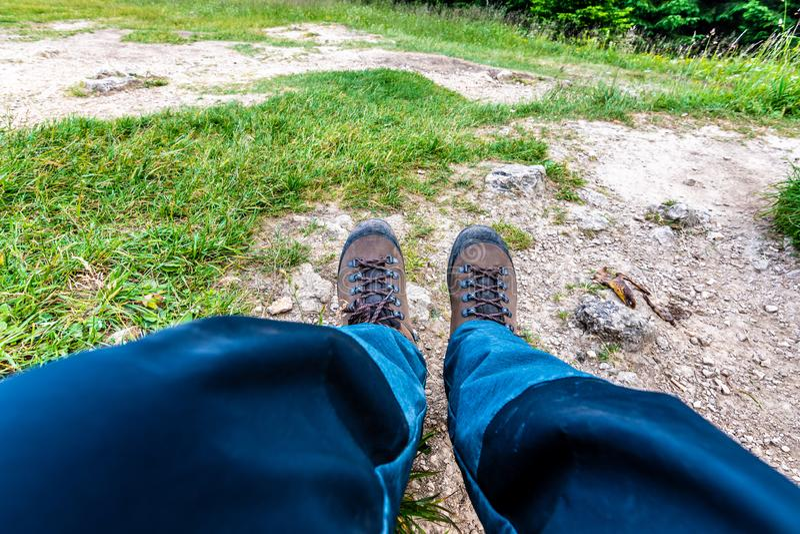 远足在地面上的起动 游人和旅客使用的可靠的鞋子为远足和迁徙 布朗颜色 免版税库存照片