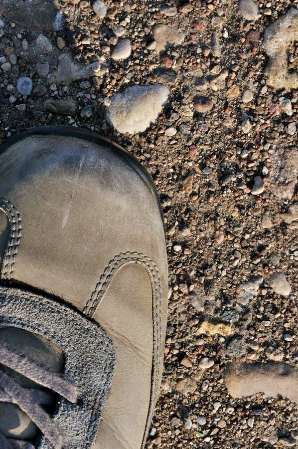 远足在坚硬干旱的旱田的起动越野鞋子,垂直光秃的地球,尘土,石头,岩石,小卵石接近的,详细的宏指令  免版税库存照片