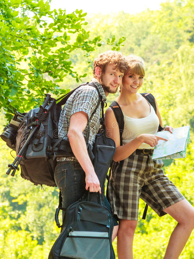 远足在旅行的挑运的夫妇读书地图 免版税库存图片