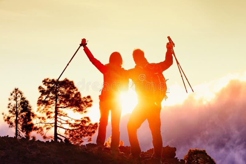 远足夫妇愉快由在成功的山日落 库存图片