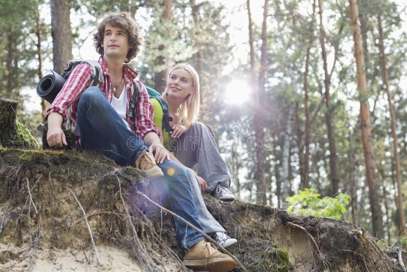 远足夫妇的年轻人坐峭壁边缘在森林里 免版税图库摄影