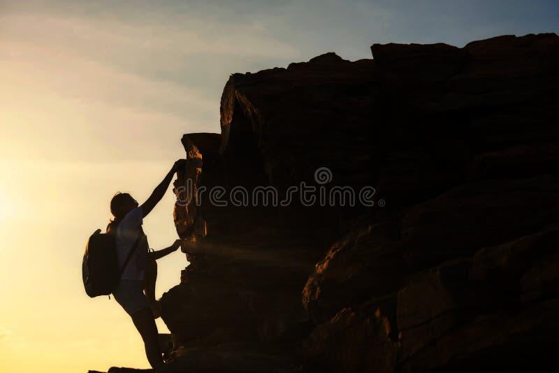 远足妇女上升冠上小山在日落 库存图片