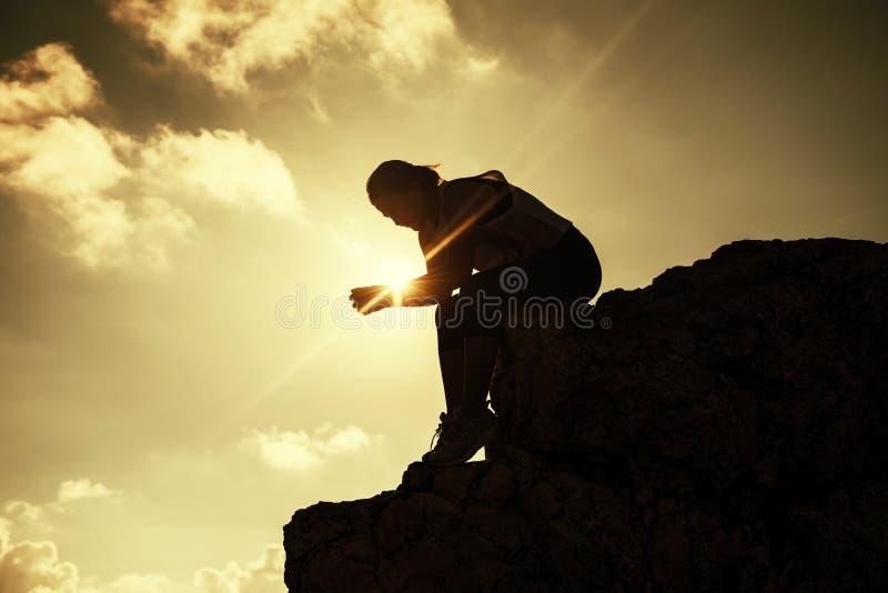 远足妇女坐小山峰顶 免版税库存图片