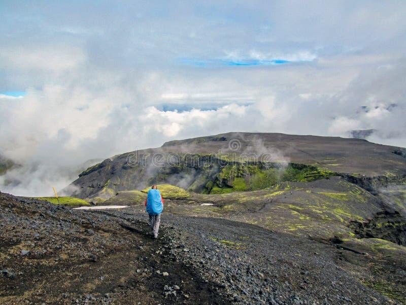 远足妇女的旅客走在冰岛高地的路与活跃重的背包旅行生活方式自由概念的冒险 库存照片