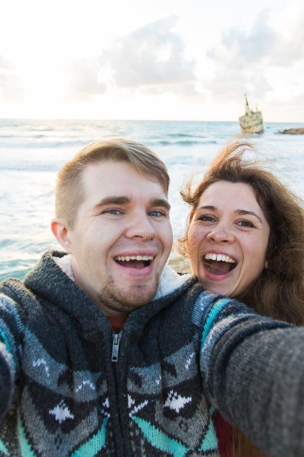 远足年轻笑的夫妇采取与巧妙的电话的selfie 愉快的年轻采取与海的人和妇女自画象或 库存照片