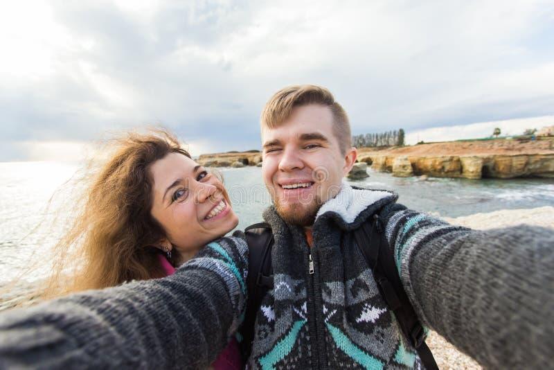 远足年轻笑的夫妇采取与巧妙的电话的selfie 愉快的年轻采取与海的人和妇女自画象或 免版税库存图片