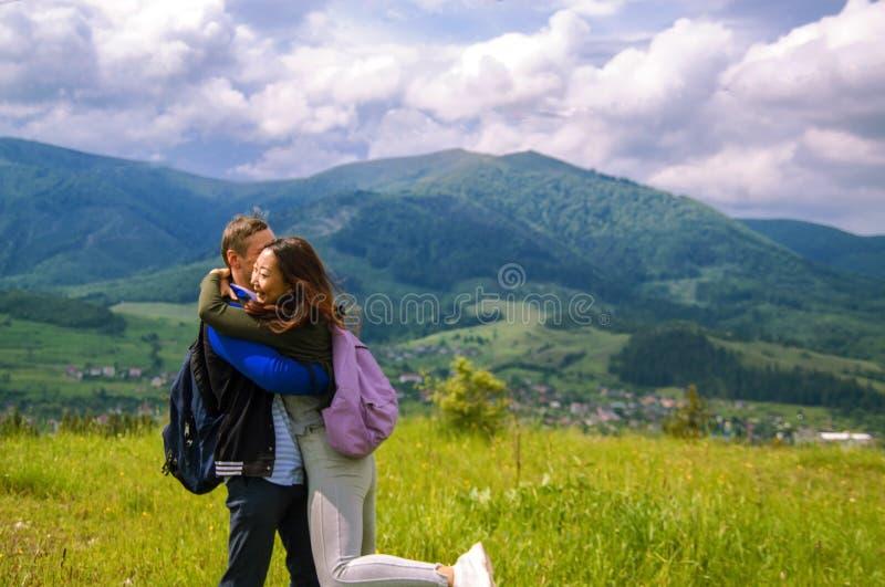 远足拥抱和笑在山顶部的夫妇背面图  库存图片