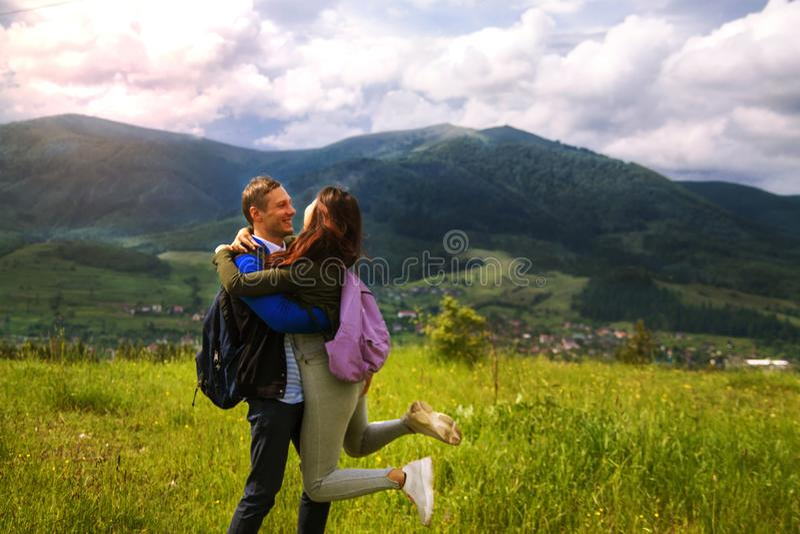 远足拥抱和笑在山顶部的夫妇背面图  免版税库存图片
