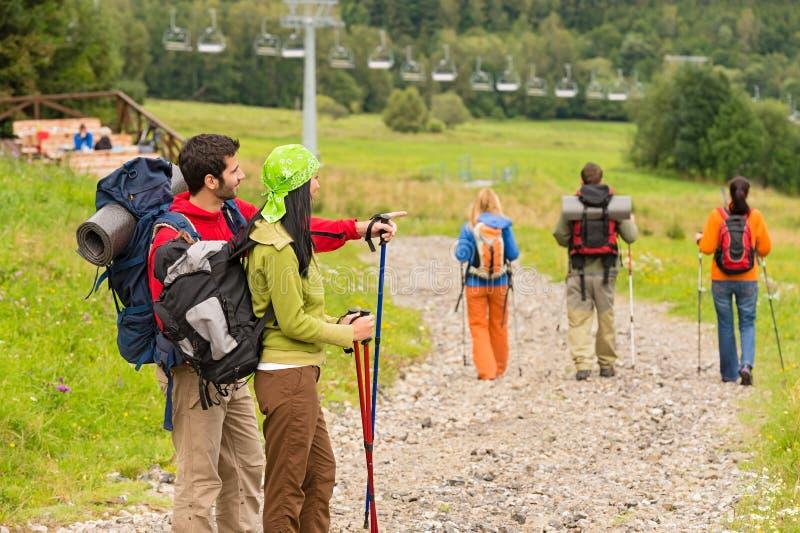 远足指向和走在道路的朋友 库存照片