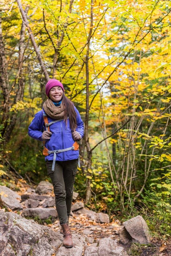 远足有背包的徒步旅行者女孩走在山的森林足迹的 秋天自然远足的亚裔妇女与背包帽子和 免版税库存图片