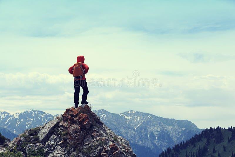 远足者享受在山上面峭壁的看法 库存照片