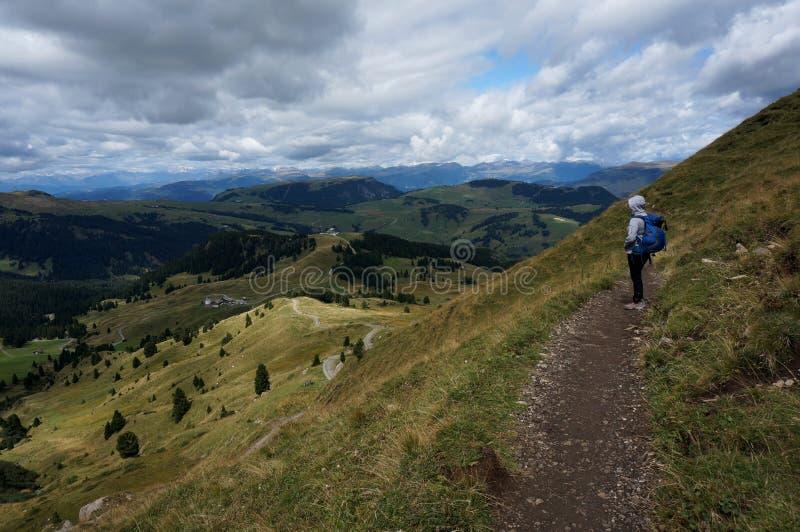 远足者享受看法ove alp de siuisi在剧烈的云彩下 免版税库存图片