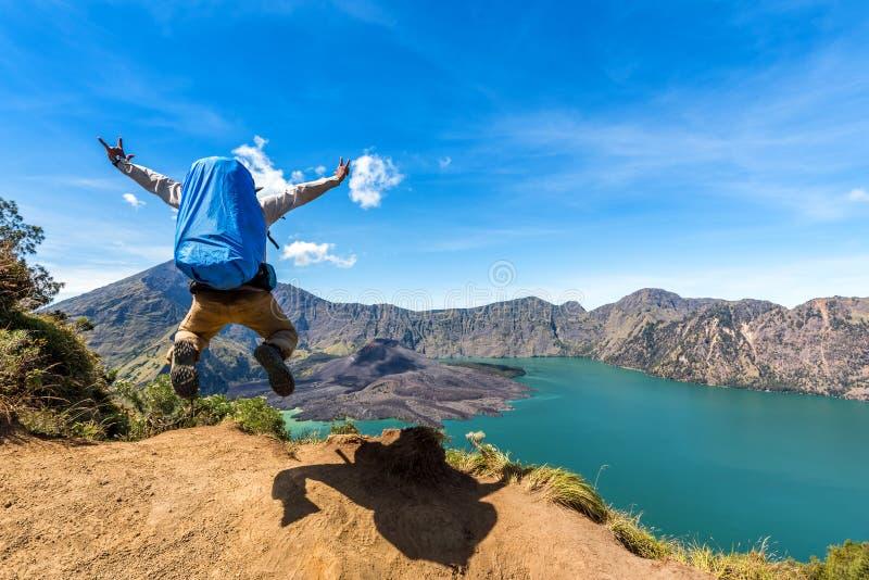 远足者人用背包传播的手和跳跃在完成上升以后在Rinjani山,龙目岛,印度尼西亚 图库摄影