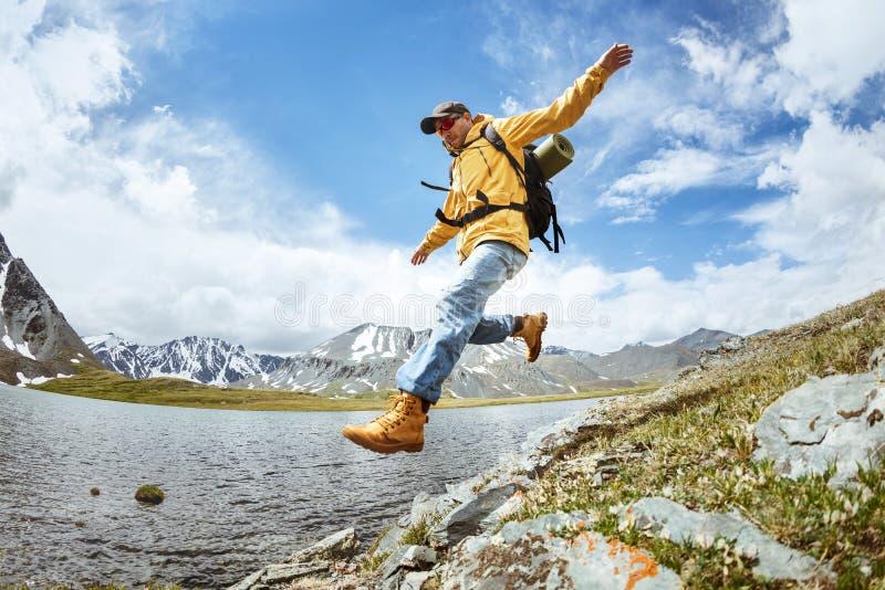 远足者从大岩石跳反对山湖 免版税库存图片