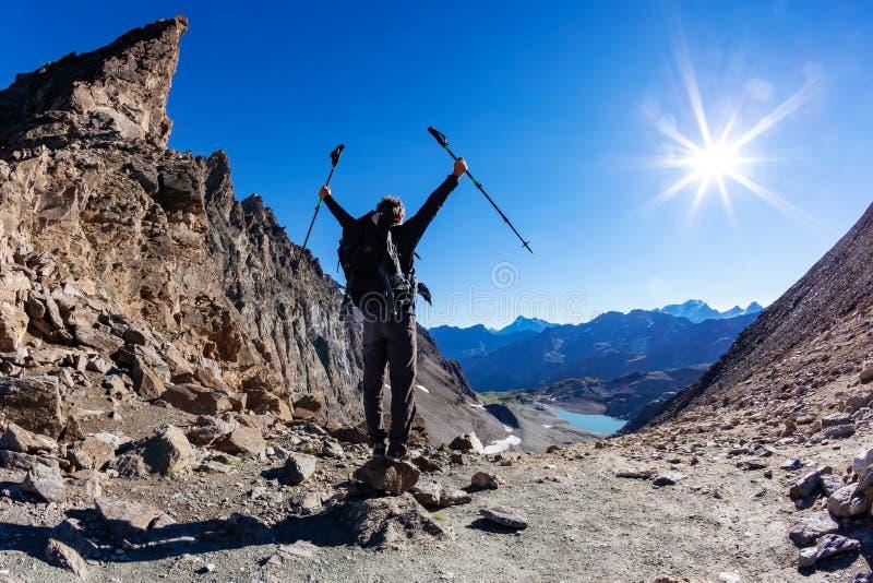 远足者到达一张高山通行证;他显示他的喜悦在开放胳膊 库存图片