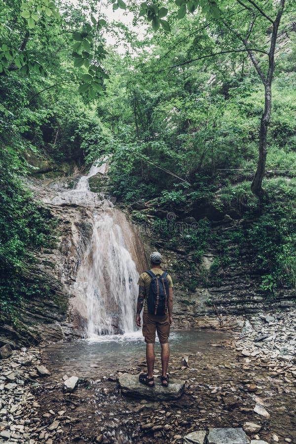 远足者到达了目的地和瀑布和秀丽未受破坏的自然享用视图  沉思冒险概念 图库摄影